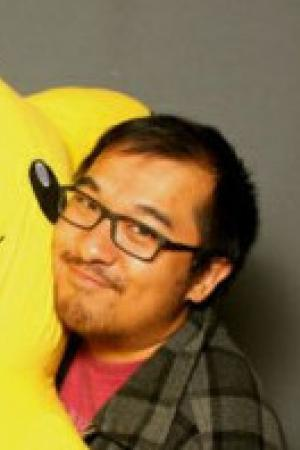 A photo of Peter Yang holding a giant, plush Pikachu.